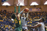 West Virginia forward Gabe Osabuohien (3) shoots while defended by Baylor forward Freddie Gillespie (33) and West Virginia forward Derek Culver (1) looks on during the second half of an NCAA college basketball game Saturday, March 7, 2020, in Morgantown, W.Va. (AP Photo/Kathleen Batten)