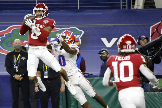 Oklahoma cornerback Woodi Washington, left, intercepts a pass in the end zone intended for Florida wide receiver Ja'Quavion Fraziars as safety Pat Fields (10) watches during the first half of the Cotton Bowl NCAA college football game in Arlington, Texas, Wednesday, Dec. 30, 2020. (AP Photo/Michael Ainsworth)
