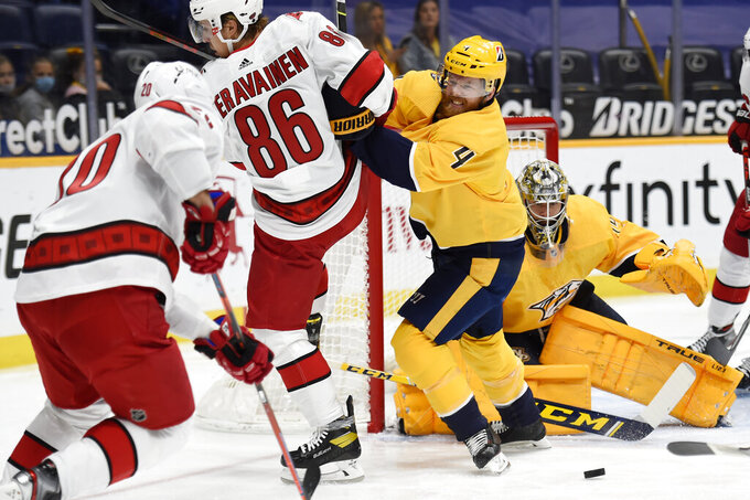Nashville Predators defenseman Ryan Ellis (4) shoves Carolina Hurricanes left wing Teuvo Teravainen (86) away from the puck during the first period of an NHL hockey game Saturday, May 8, 2021, in Nashville, Tenn. (AP Photo/Mark Zaleski)