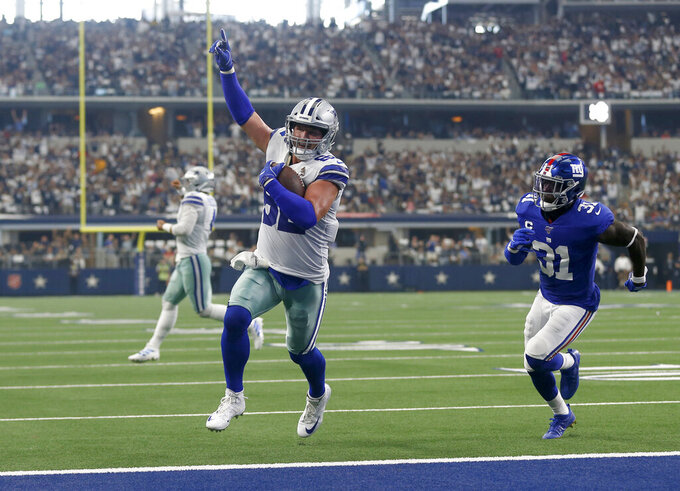 FILE - In this Sept. 8, 2019 file photo, Dallas Cowboys tight end Jason Witten (82) celebrates catching a touchdown pass as New York Giants defensive back Michael Thomas (31) defends in the first half of a NFL football game in Arlington, Texas. Witten is returning to Monday Night Football in his more accustomed role as the Dallas Cowboys' tight end and not a television analyst for the ESPN production. Witten didn't know if ESPN asked to have him miked for the game, but wanted no part of it. He said he has done it before and he didn't like. His focus this week is to help the Cowboys build for their big win over the Eagles two weeks ago. (AP Photo/Ron Jenkins, File)