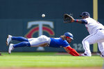 Toronto Blue Jays shortstop Bo Bichette, left, dives safely into first base as Minnesota Twins first baseman Miguel Sano (22) waits for the ball in the third inning of a baseball game, Sunday, Sept. 26, 2021, in St. Paul, Minn. (AP Photo/Andy Clayton-King)