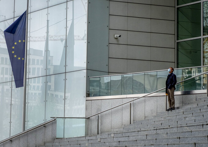 A man with a face mask walks stands on the stairs of the Commerzbank building in Frankfurt, Germany, Thursday, April 29, 2021. (AP Photo/Michael Probst)