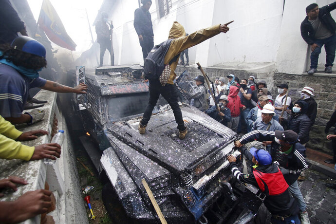 Anti-government demonstrators commandeer an armored vehicle during a nationwide strike against President Lenin Moreno and his economic policies, in Quito, Ecuador, Wednesday, Oct. 9, 2019. Big jumps in the costs of gasoline and diesel after Moreno ended subsidies last week set off the upheaval, but other complaints have come out amid the protests, looting, vandalism, clashes with security forces, the blocking of highways and disruptions of Ecuador's vital oil industry. (AP Photo/Carlos Noriega)