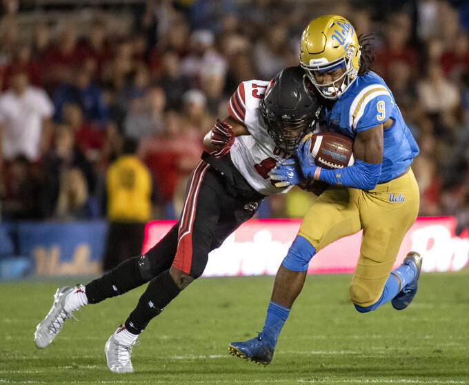 UCLA wide receiver Dymond Lee, right, is tackled by Utah defensive back Corrion Ballard during the first half of an NCAA college football game Friday, Oct. 26, 2018, in Pasadena, Calif. (AP Photo/Kyusung Gong)