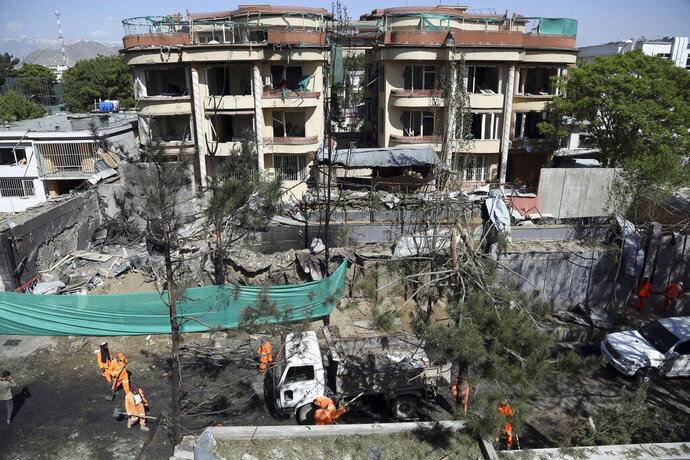 Afghan municipality workers clean debris in front of the damaged buildings a day after an attack in Kabul, Afghanistan, Thursday, May 9, 2019. Taliban fighters attacked the offices of a U.S.-based aid organization in the Afghan capital on Wednesday, setting off a huge explosion and battling security forces in an assault, the Interior Ministry said. (AP Photo/Rahmat Gul)