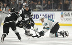 San Jose Sharks center Lukas Radil, right, falls as he tries to pass the puck while under pressure from Los Angeles Kings left wing Brendan Leipsic, left, and center Trevor Lewis during the second period of an NHL hockey game Thursday, March 21, 2019, in Los Angeles. (AP Photo/Mark J. Terrill)