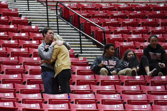 San Diego State fans hug in the stands after an NCAA college basketball game against UNLV, Saturday, Feb. 22, 2020, in San Diego. (AP Photo/Denis Poroy)