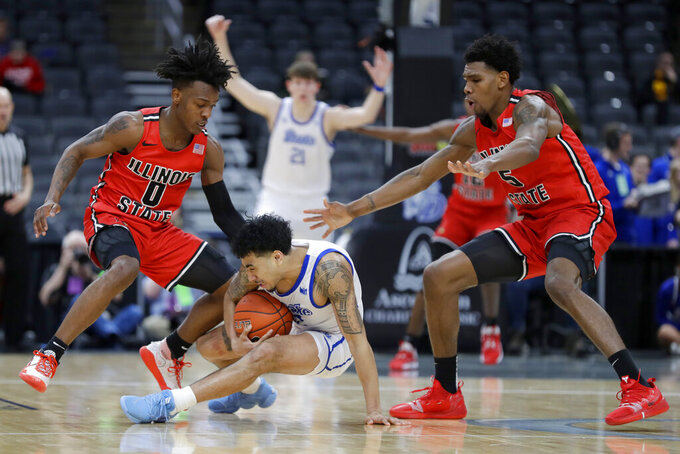 Drake's Roman Penn, center, falls with the ball as Illinois State's DJ Horne (0) and Keith Fisher III (5) defend during the second half of an NCAA college basketball game in the first round of the Missouri Valley Conference men's tournament Thursday, March 5, 2020, in St. Louis. (AP Photo/Jeff Roberson)