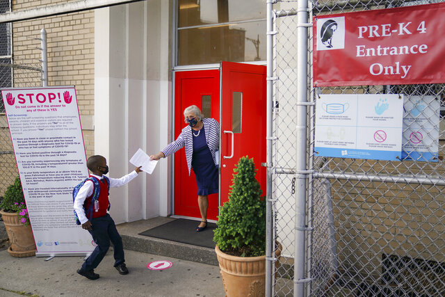 FILE - In this Sept. 9, 2020, file photo, a student wears a protective masks as they arrive for classes at the Immaculate Conception School while observing COVID-19 prevention protocols in The Bronx borough of New York. New York City has again delayed the planned start of in-person learning for most of the more than 1 million students in its public school system. Mayor Bill de Blasio announced Thursday, Sept. 17,  that most elementary school students would do remote-only learning until Sept. 29. Middle and high schools would stay remote through Oct. 1.(AP Photo/John Minchillo)