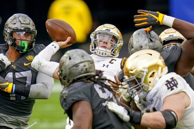 Notre Dame quarterback Ian Book (12) gets a pass away as Pittsburgh defensive lineman Rashad Weaver (17) and the Pitt defense pressure him during the first half of an NCAA college football game, Saturday, Oct. 24, 2020, in Pittsburgh. (AP Photo/Keith Srakocic)