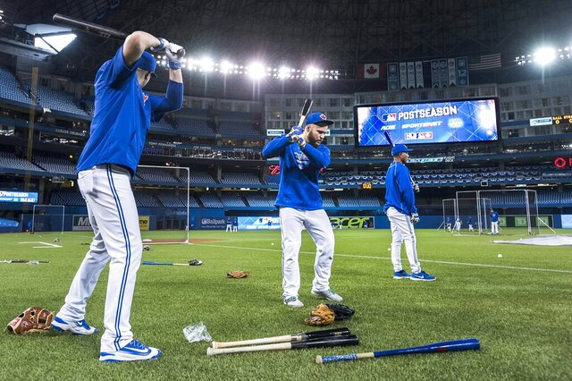 FILE - In this Oct. 7, 2015, file photo, Toronto Blue Jays Russell Martin, center, and Troy Tulowitzki, left, prepare to take batting practice during a team workout at the Rogers Centre in Toronto. All 30 Major League Baseball teams will train at their regular-season ballparks for the pandemic-shortened season after the Blue Jays received a Canadian federal government exemption on Thursday, July 2, 2020, to work out at Rogers Centre. Toronto will move camp from its spring training complex in Dunedin, Fla., where players reported for intake testing. The Blue Jays will create a quarantine environment at Rogers Centre and the adjoining Toronto Marriott City Centre Hotel which overlooks the field. (Darren Calabrese/The Canadian Press via AP, File)