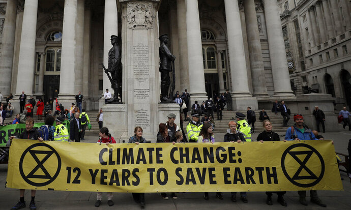 FILE - In this Thursday, April 25, 2019 file photo, Extinction Rebellion climate change protesters hold up a banner near the Bank of England, in the City of London. The environmental activist group Extinction Rebellion has postponed a plan to shut down London's Heathrow Airport with drones after it was criticized by politicians and police. The anti-climate change group said Sunday, June 16 it would
