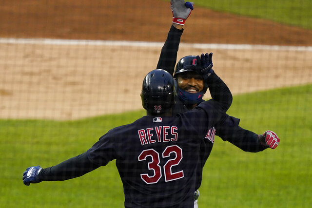 Cleveland Indians' Domingo Santana is greeted by Franmil Reyes after hitting a three-run home run during the fourth inning of a baseball game against the Detroit Tigers, Friday, Aug. 14, 2020, in Detroit. (AP Photo/Carlos Osorio)