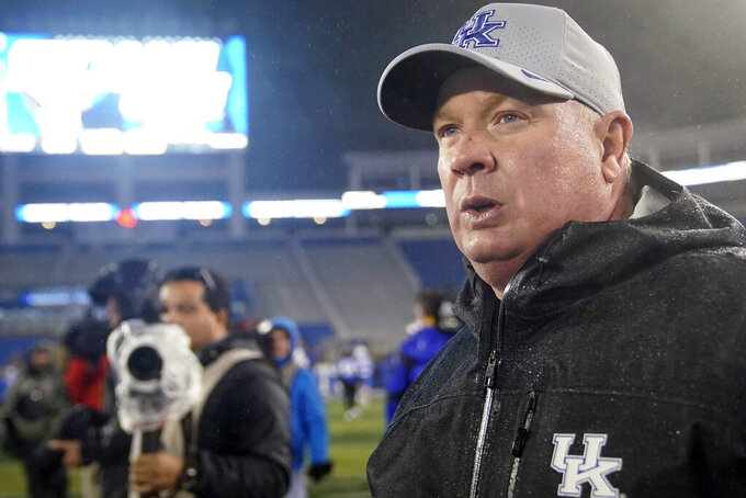 FILE - In this  Saturday, Nov. 23, 2019 file photo, Kentucky coach Mark Stoops walks onto the field after the the NCAA college football game against UT Martin in Lexington, Ky. The Wildcats' schedule got much tougher last month when they added a road date with Alabama as well as a home game with Ole Miss. Kentucky won't play Louisville due to the SEC-only schedule, but its other three non-conference games would have been against Group of Five or Football Championship Subdivision programs: Eastern Michigan, Kent State and Eastern Illinois.(AP Photo/Bryan Woolston, File)