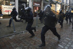 Riot police officers charge Thursday, Jan. 9, 2020 during a protest in Lille, northern France. Rail workers, teachers, doctors, lawyers and others joined a nationwide day of protests and strikes Thursday to denounce French President Emmanuel Macron's plans to overhaul the pension system. (AP Photo/Michel Spingler)