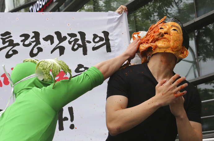In this Wednesday, July 17, 2019, file photo, a protester throws kimchi, South Korean traditional pungent vegetable, to his fellow protester wearing a mask of Japanese Prime Minister Shinzo Abe during a rally, protesting against the Japanese government's trade restriction to South Korea, in front of the Japanese Embassy in Seoul. (AP Photo/Ahn Young-joon, File)