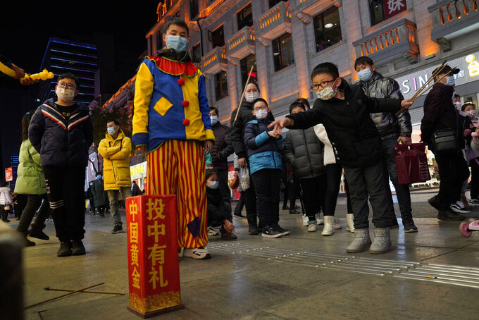 FILE - In this Jan. 15, 2021, file photo, a child attempts to throw sticks into a container to win prizes along a shopping street in Wuhan in central China's Hubei province. Couples go on dates, families dine out at restaurants, shoppers flock to stores. Face masks aside, people are going about their daily life pretty much as before in the Chinese city that was first hit by the COVID-19 pandemic. (AP Photo/Ng Han Guan, File)