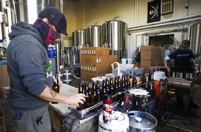 Aaron Buckner and Jordan Vigil bottle beer at Epic Brewing Co. in Salt Lake City, Thursday, Oct. 29, 2020. (Rick Egan/The Salt Lake Tribune via AP)