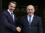 Greece's Prime Minister Kyriakos Mitsotakis, left, welcomes his Israeli counterpart Benjamin Netanyahu in Athens, Thursday, Jan. 2, 2020. The leaders of Greece, Israel and Cyprus will meet in Athens Thursday to sign a deal aiming to build a key undersea pipeline, named EastMed, designed to carry gas from new rich offshore deposits in the southeastern Mediterranean to continental Europe.(AP Photo/Yorgos Karahalis)