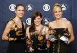 FILE - In this Feb. 11, 2007 file photo, musicians Emily Robison, left, Natalie Maines, center, and Martie Maguire of the group The Dixie Chicks pose with their awards for song of the year, for record of the year, for album of the year, for best country album, and for best country performance at the 49th Annual Grammy Awards in Los Angeles. The group have dropped the word dixie from their name and are now going by The Chicks. The move follows a decision by country group Lady Antebellum to change to Lady A after acknowledging the word's association to slavery. (AP Photo/Kevork Djansezian, File)
