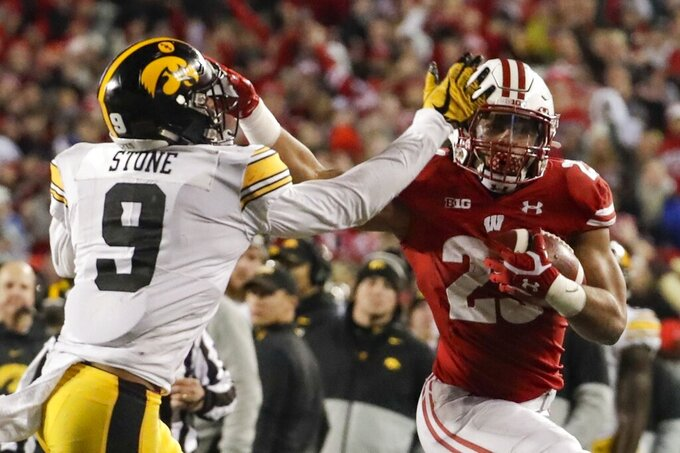 Wisconsin's Jonathan Taylor tries to get past Iowa's Geno Stone during the second half of an NCAA college football game Saturday, Nov. 9, 2019, in Madison, Wis. Wisconsin won 24-22. (AP Photo/Morry Gash)