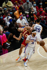 Philadelphia 76ers guard Seth Curry (31) carries the ball as Philadelphia 76ers guard Ben Simmons (25) clashes with Hawks guard Bogdan Bogdanovic (13) during the second half of Game 3 of a second-round NBA basketball playoff series, Friday, June 11, 2021, in Atlanta. (AP Photo/John Bazemore)