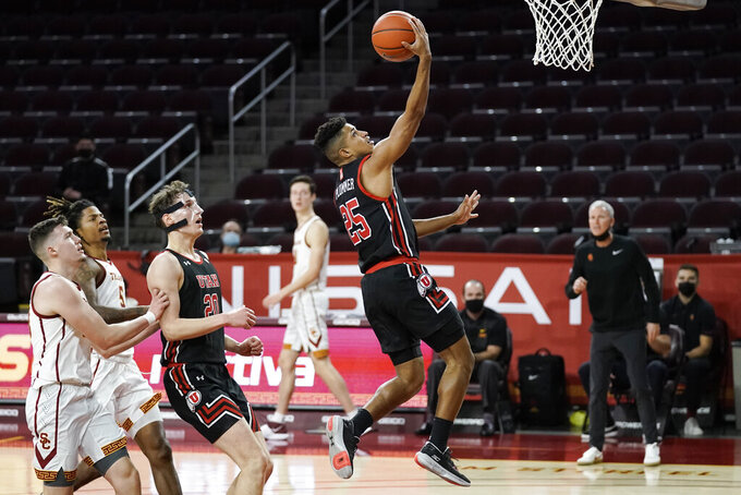 Utah's Alfonso Plummer, center, drives to the basket during the first half of an NCAA college basketball game against Southern California, Saturday, Jan. 2, 2021, in Los Angeles. (AP Photo/Jae C. Hong)