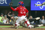 Texas Rangers catcher Jose Trevino (23) looks for the call after San Diego Padres Eric Hosmer (30) slid home during the first inning of a baseball game Friday, April 9, 2021, in Arlington, Texas. Hosmer was ruled safe after a review. (AP Photo/Richard W. Rodriguez)