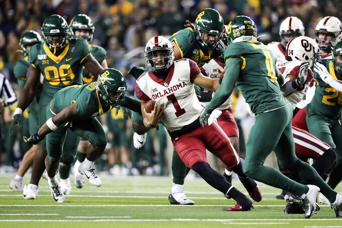 Oklahoma quarterback Jalen Hurts (1) carries the ball as he cuts back on Baylor cornerback Jameson Houston, right, during the second half of an NCAA college football game in Waco, Texas, Saturday, Nov. 16, 2019. Oklahoma won 34-31. (AP Photo/Ray Carlin)