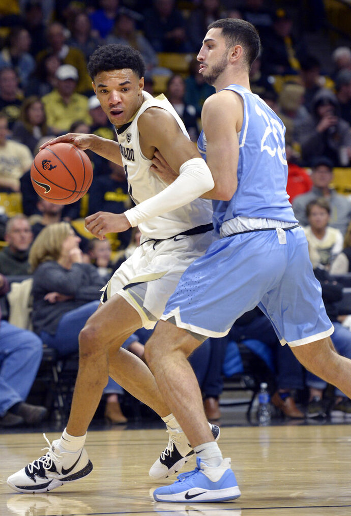 Colorado guard Tyler Bey tries to get around San Diego forward Jared Rodriguez during the first half of an NCAA college basketball game Saturday, Nov. 16, 2019, in Boulder, Colo. (AP Photo/Cliff Grassmick)