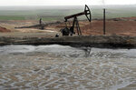 FILE - This March 27, 2018 file photo shows a pond of oil at an oil field controlled by a U.S-backed Kurdish group, in Rmeilan, Hassakeh province, Syria. As a fuel shortage crisis deepens in government-held areas of Syria, Cabinet ministers huddled in televised meetings to reassure the public they are searching for solutions. New rationing measures were rolled out, and government officials held talks with allies in Iran and Russia to explore options for the crisis aggravated by U.S. sanctions on Damascus and Tehran. (AP Photo/Hussein Malla, File)