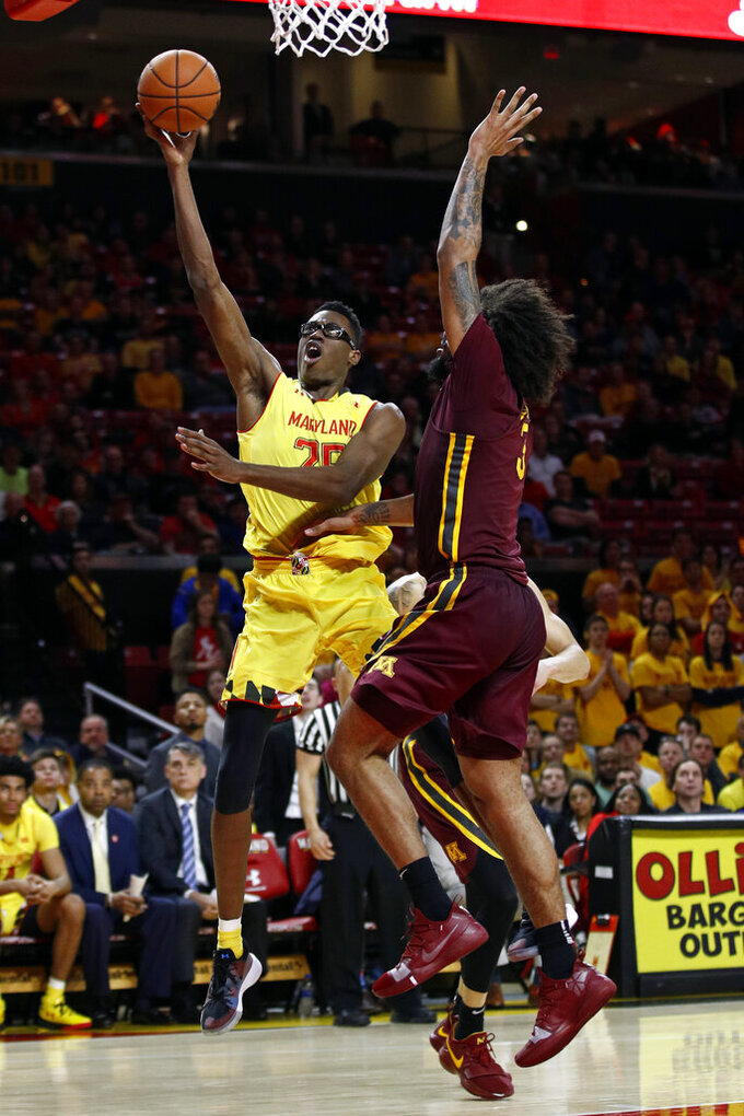 Maryland forward Jalen Smith, left, shoots against Minnesota forward Jordan Murphy in the second half of an NCAA college basketball game, Friday, March 8, 2019, in College Park, Md. (AP Photo/Patrick Semansky)