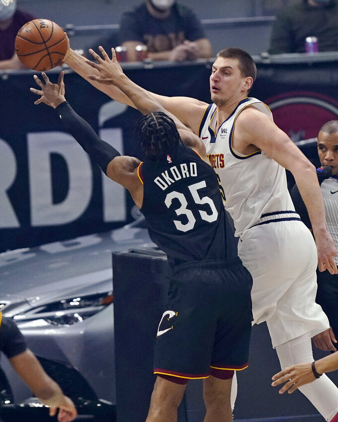 Denver Nuggets' Nikola Jokic, right, passes the ball as Cleveland Cavaliers' Isaac Okoro defends during the first half of an NBA basketball game Friday, Feb. 19, 2021, in Cleveland. (AP Photo/Tony Dejak)