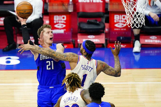 Orlando Magic's Moritz Wagner (21) goes up for a shot against Philadelphia 76ers' Mike Scott (1) during the second half of an NBA basketball game, Sunday, May 16, 2021, in Philadelphia. (AP Photo/Matt Slocum)