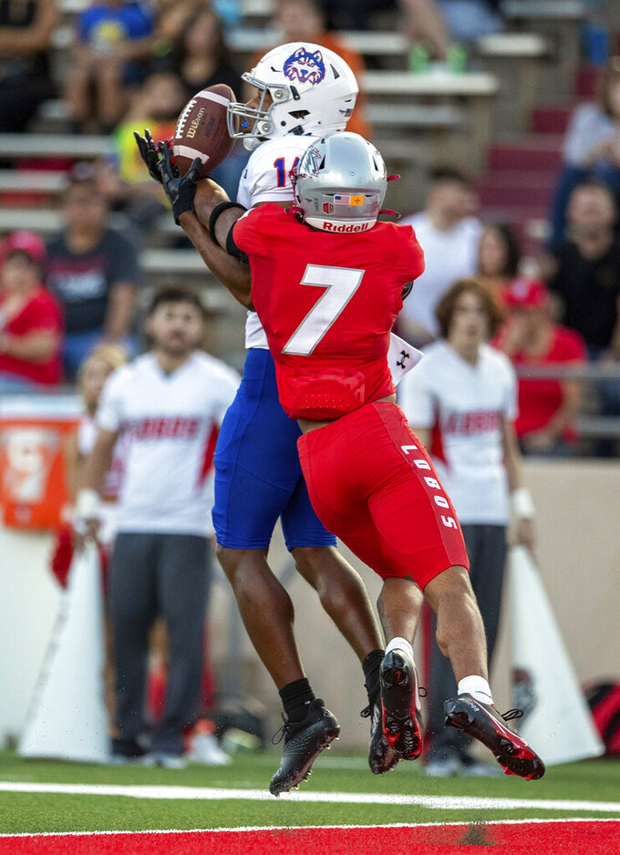 New Mexico safety Tavian Combs (7) breaks up a pass intended for Houston Baptist wide receiver Vernon Harrell during the first half of an NCAA college football game Thursday, Sept. 2, 2021, in Albuquerque, N.M. (AP Photo/Andres Leighton)