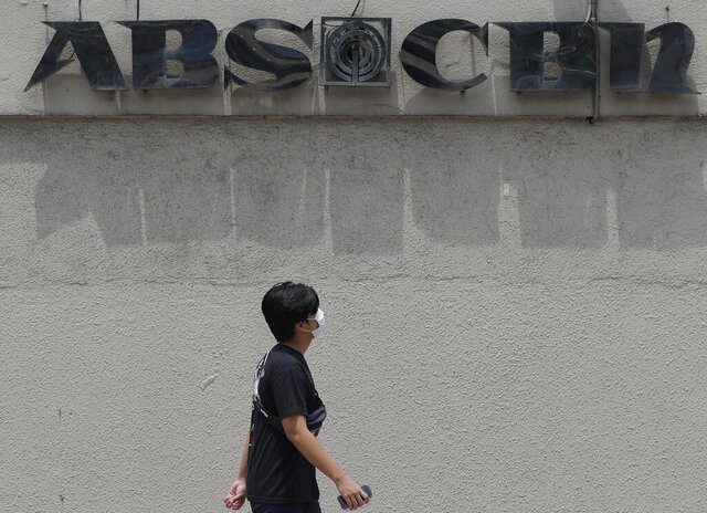FILE - In this May 6, 2020, file photo, a man wearing a mask passes by the headquarters of broadcast network ABS-CBN Corp. in Manila, Philippines. The Philippines' largest TV network aired its final newscasts Friday, Aug. 28, 2020 to millions of provincial viewers with anchors tearfully bidding goodbye after lawmakers voted to reject its license renewal despite a raging coronavirus pandemic. (AP Photo/Aaron Favila, File)