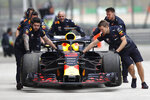 The car of Red Bull driver Daniel Ricciardo of Australia is pushed back to his team's garage after an engine trouble during the third practice session for the Chinese Formula One Grand Prix at the Shanghai International Circuit in Shanghai, Saturday, April 14, 2018. (AP Photo)
