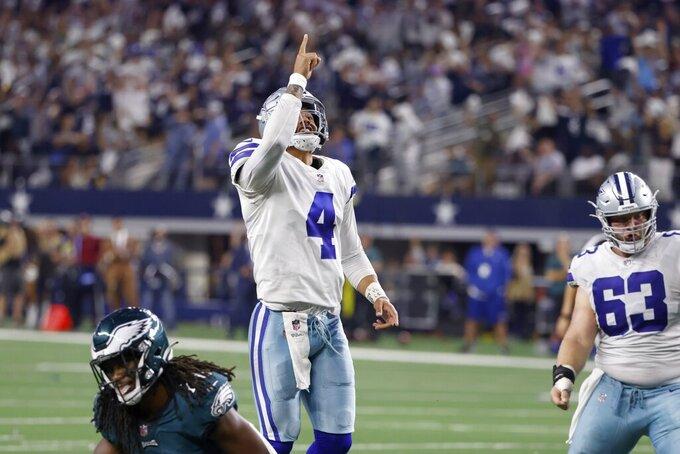 Dallas Cowboys quarterback Dak Prescott (4) and center Tyler Biadasz (63) celebrate a touchdown scored by Dalton Schultz in the second half of an NFL football game against the Philadelphia Eagles in Arlington, Texas, Monday, Sept. 27, 2021. (AP Photo/Ron Jenkins)