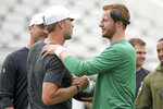 Jacksonville Jaguars quarterback Nick Foles, front left, greets Philadelphia Eagles quarterback Carson Wentz before an NFL preseason football game, Thursday, Aug. 15, 2019, in Jacksonville, Fla. (AP Photo/Stephen B. Morton)