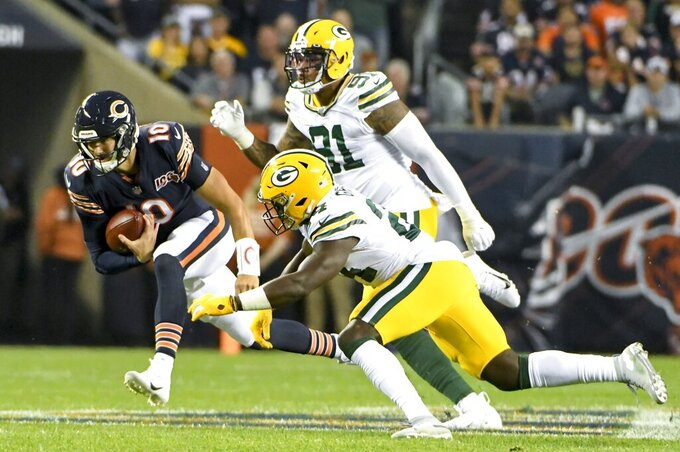 Chicago Bears' Mitchell Trubisky runs past Green Bay Packers' Raven Greene and Preston Smith during the first half of an NFL football game Thursday, Sept. 5, 2019, in Chicago. (AP Photo/David Banks)