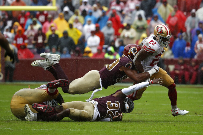 San Francisco 49ers running back Matt Breida, right, rushes past Washington Redskins inside linebacker Jon Bostic, top, and cornerback Jimmy Moreland (32) in the first half of an NFL football game, Sunday, Oct. 20, 2019, in Landover, Md. (AP Photo/Alex Brandon)