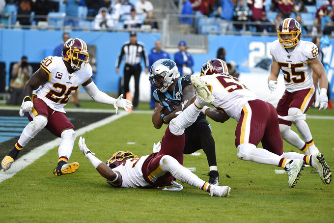 Washington Redskins free safety Montae Nicholson, inside linebacker Jon Bostic, right, and strong safety Landon Collins (20) stop Carolina Panthers wide receiver D.J. Moore (12) late in the second half of an NFL football game in Charlotte, N.C., Sunday, Dec. 1, 2019. (AP Photo/Mike McCarn)