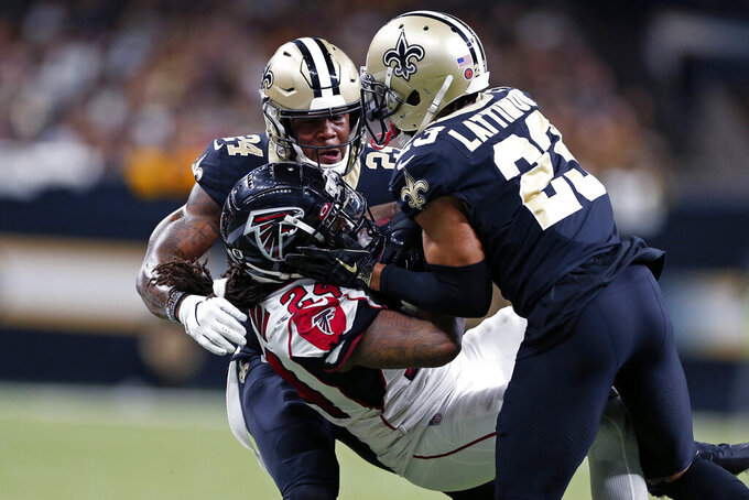 Atlanta Falcons running back Devonta Freeman (24) is tackled by New Orleans Saints cornerback Marshon Lattimore (23) and strong safety Vonn Bell (24) in the first half of an NFL football game in New Orleans, Sunday, Nov. 10, 2019. (AP Photo/Rusty Costanza)
