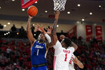 Tulsa's Martins Igbanu, left, goes up for a shot as Houston's Chris Harris Jr., center, and Fabian White Jr., right, defend during the second half of an NCAA college basketball game Wednesday, Feb. 19, 2020, in Houston. (AP Photo/David J. Phillip)