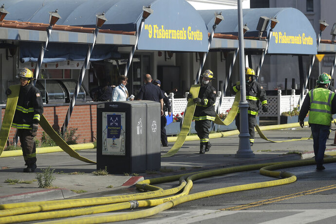 Fire officials carry a hose in front of The Grotto restaurant after a fire broke out before dawn at Fisherman's Wharf in San Francisco, Saturday, May 23, 2020. A warehouse was destroyed. Fire officials said no injuries have been reported Saturday morning and firefighters are making multiple searches to ensure no one was inside the building on Pier 45. (AP Photo/Jeff Chiu)