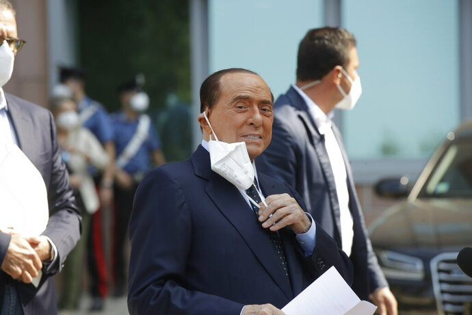 Italian former Premier Silvio Berlusconi adjusts his face mask as he leaves the San Raffaele hospital in Milan, Italy, Monday, Sept. 14, 2020. Berlusconi had been hospitalized as a precaution to monitor his coronavirus infection after testing positive for COVID-19. (AP Photo/Luca Bruno)