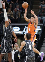 Phoenix Suns' Devin Booker (1) passes the ball as he is defended by San Antonio Spurs' LaMarcus Aldridge (12) and Derrick White during the first half of an NBA basketball game, Friday, Jan. 24, 2020, in San Antonio. (AP Photo/Darren Abate)