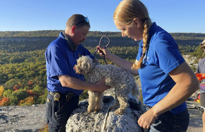 In this photo provided by New York State Parks on Wednesday, Oct. 13, 2021, Ulster County SPCA Executive Director Gina Carbonari, right, and SPCA Supervisor Chris West, left, check a rescued a 12-year-old dog named Liza, found trapped after five days deep inside the narrow, rocky crevice at Minnewaska State Park Preserve in Kerhonkson, N.Y. A dog trapped for five days deep inside a narrow, rocky crevice at a state park north of New York City was rescued unharmed — though it was hungry and thirsty, parks officials said Wednesday. (New York State Parks via AP)