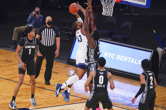 Villanova forward Eric Dixon (43) goes to the basket against Georgetown center Timothy Ighoefe (5) during the first half of an NCAA college basketball game in the quarterfinals of the Big East conference tournament, Thursday, March 11, 2021, in New York. (AP Photo/Mary Altaffer)