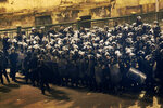 FILE - In this Jan. 26, 2011 file photo, Egyptian riot police group push back protesters, during clashes in downtown Cairo, Egypt. The 2011 uprising led to the quick ouster of autocrat Hosni Mubarak. A decade later, thousands are estimated to have fled abroad to escape a state, headed by President Abdel Fattah el-Sissi, that is even more oppressive. (AP Photo/Ben Curtis, File)